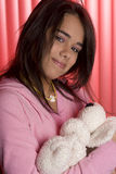 Cradling her baby. Teen girl in pink pajama cradling a teddy bear Royalty Free Stock Photo