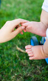 Cradling infant. Mother's hands cradling her infant son's feet, close-up Royalty Free Stock Photos