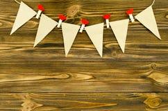 Craft as bandeiras de papel com a festão decorativa do partido dos pinos no woode Imagem de Stock