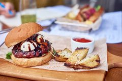 Craft beef burger and french fries on wooden table with potato stock photography