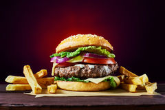 Craft beef burgers. Craft beef burger and french fries on wooden table isolated on dark red background Royalty Free Stock Image