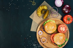 Craft beef burgers. Top view. Craft beef burgers on round wooden cutting board with vegetables. Flat lay on black textured background Royalty Free Stock Image