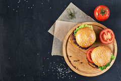 Craft beef burgers. Top view. Craft beef burgers on round wooden cutting board with vegetables. Flat lay on black textured background Stock Photo