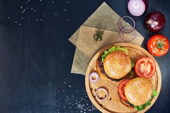 Craft beef burgers. Top view. Craft beef burgers on round wooden cutting board with vegetables. Flat lay on black textured background Stock Image