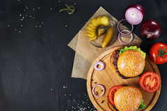 Craft beef burgers. Top view. Craft beef burgers on round wooden cutting board with vegetables. Flat lay on black textured background Stock Photography
