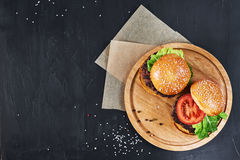 Craft beef burgers. Top view. Craft beef burgers on round wooden cutting board with vegetables. Flat lay on black textured background Stock Photos