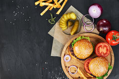 Craft beef burgers. Top view. Craft beef burgers on round wooden cutting board with vegetables and french fries. Flat lay on black textured background Stock Photo