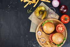 Craft beef burgers. Top view. Craft beef burgers on round wooden cutting board with vegetables and french fries. Flat lay on black textured background Royalty Free Stock Images