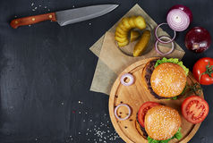 Craft beef burgers. Top view. Craft beef burgers on round wooden cutting board with vegetables and knife. Flat lay on black textured background Stock Photo