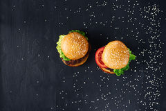 Craft beef burgers. Top view. Craft beef burgers with vegetables. Flat lay on black textured background with sesame seeds Stock Photos