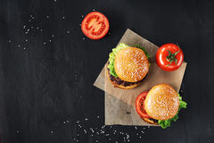 Craft beef burgers. Top view. Craft beef burgers with vegetables. Flat lay on black textured background with sesame seeds Stock Images
