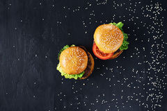 Craft beef burgers. Top view. Craft beef burgers with vegetables. Flat lay on black textured background with sesame seeds Royalty Free Stock Photography
