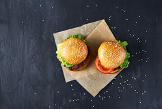 Craft beef burgers. Top view. Craft beef burgers with vegetables. Flat lay on black textured background with sesame seeds Royalty Free Stock Image