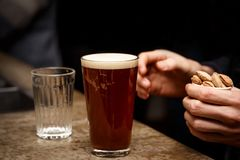 Craft Beer in Bar, 0.4 liter glass. Hand with nuts, snacks in the frame. royalty free stock image