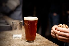 Craft Beer in Bar, 0.4 liter glass. Hand with nuts, snacks in the frame. stock photos