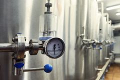 Craft beer brewing equipment in brewery. Metal tanks, alcoholic drink production. Facilities in modern interior of brewery. Manufacturable process of brewage royalty free stock photo