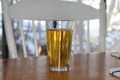 Craft beer in pint glass. Beer on table. White chair at table and view out window in the background Stock Image