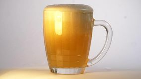 Craft beer is poured into a mug. Beer Foam overflows over the edge of the mug. Lots of froth. Cold Light  Beer is pouring stock video