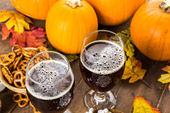 Craft beer. Craft pumpkin beer in beer glasses with salty pretzels and popcorn royalty free stock photography