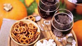 Craft beer. Craft pumpkin beer in beer glasses with salty pretzels and popcorn stock video