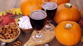 Craft beer. Craft pumpkin beer in beer glasses with salty pretzels and popcorn stock footage