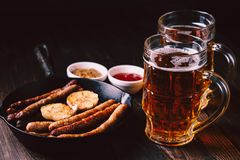 Craft beer and sausages.oktoberfest food, pub. Beer and appetizing snacks. table with two mugs of craft lager and frying pan with homemade grilled sausages royalty free stock images