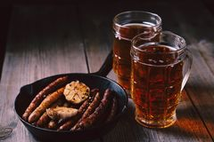 Craft beer and sausages.oktoberfest food, pub. Beer and appetizing snacks. table with two mugs of craft lager and frying pan with homemade grilled sausages stock photos