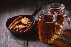 Craft beer and sausages.oktoberfest food, pub. Beer and appetizing snacks. table with two mugs of craft lager and frying pan with homemade grilled sausages royalty free stock photography