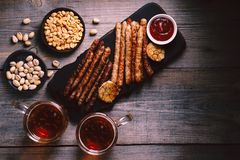 Craft beer and sausages.oktoberfest food, pub. Beer and appetizing snacks. table with two mugs of lager, wooden board with grilled sausages, garlic and sauce royalty free stock photography