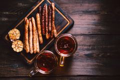 Craft beer and sausages.oktoberfest food, pub. Beer and appetizing snacks. table with two mugs of craft lager, wooden board with homemade grilled sausages stock images