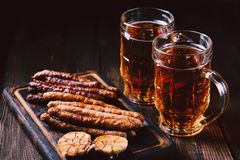 Craft beer and sausages.oktoberfest food, pub. Beer and appetizing snacks. table with two mugs of craft lager, wooden board with homemade grilled sausages royalty free stock image