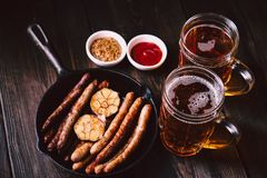 Craft beer and sausages.oktoberfest food, pub. Beer and snacks. bar table. restaurant, pub, oktoberfest food. two mugs of craft lager and frying pan with royalty free stock photo