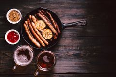 Craft beer and sausages.oktoberfest food, pub. Beer and snacks. bar table. restaurant, pub, oktoberfest food. two mugs of craft lager and frying pan with stock image