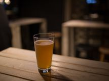 Craft beer on a table in the pub. Craft beer in a pub, on a table, focus on glass of beer Royalty Free Stock Photo