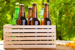Craft beer on wooden boxon blurred forrest background, summer drinks,coloured bottles.  royalty free stock images