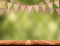 Craft brown flag banner hang over wood table with blur green tree bokeh background, Template mock up for montage. Of product.party garland holiday backdrop for stock photo