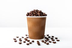 Craft coffee cup full of coffee bean on white background. Craft coffee cup full with coffee beans isolated on white bakcground. Studio light. Food photo. Good royalty free stock image