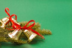 Xmas bells with red ribbons, pine branch on green background. Copy space. Closeup Stock Image