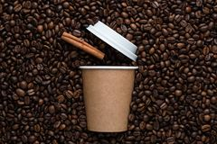 Craft disposable cup of coffee to go with a cinnamon stick on the background of roasted beans stock photos