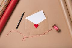 Craft envelope with blank paper, pen and red heart on beige background. Love concept. Saint Valentine`s Day concept. Mother`s day concept. Flatlay stock photography