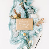 Craft envelope `happy summer cards` on blue textile with stones, dry rose and branches on white background Royalty Free Stock Image