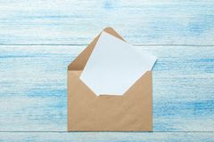 Craft envelopes with blank for text on a blue wooden table. top view royalty free stock images