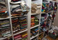 Craft and fabric room. A wall full of shelves of colorful sewing and quilting fabric and knitting wool in a craft room Royalty Free Stock Photo