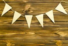 Craft a festão de papel do partido das bandeiras no fundo de madeira Fotografia de Stock