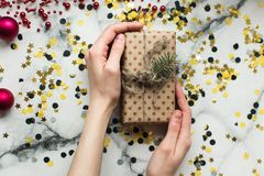 Craft gift with a bow of twine and a sprig of Christmas tree in the hands of a girl without manicure on a marble background with