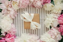Craft gift box and peonies frame flat lay on rustic table cloth. Happy mothers day. Peony border and present top view on table. International Womens Day royalty free stock photography