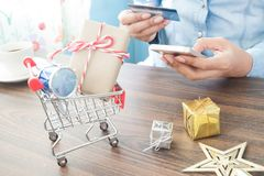 Craft gift box in shopping cart and Christmas gift with woman holding mobile phone and credit card Stock Photography