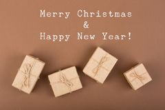 "Gift boxes on brown paper with text ""Merry Christmas & Happy new year"" background. Craft gift boxes on brown paper with text ""Merry Christmas & stock photos"