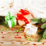 Craft gift boxes with color ribbon and bow, green Christmas tree, decorations, white plaid on wooden background. Xmas and New Year Stock Photography