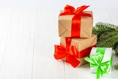 Craft gift boxes with red, green ribbon and bow, green Christmas tree, decorations, on white wooden background. Royalty Free Stock Image